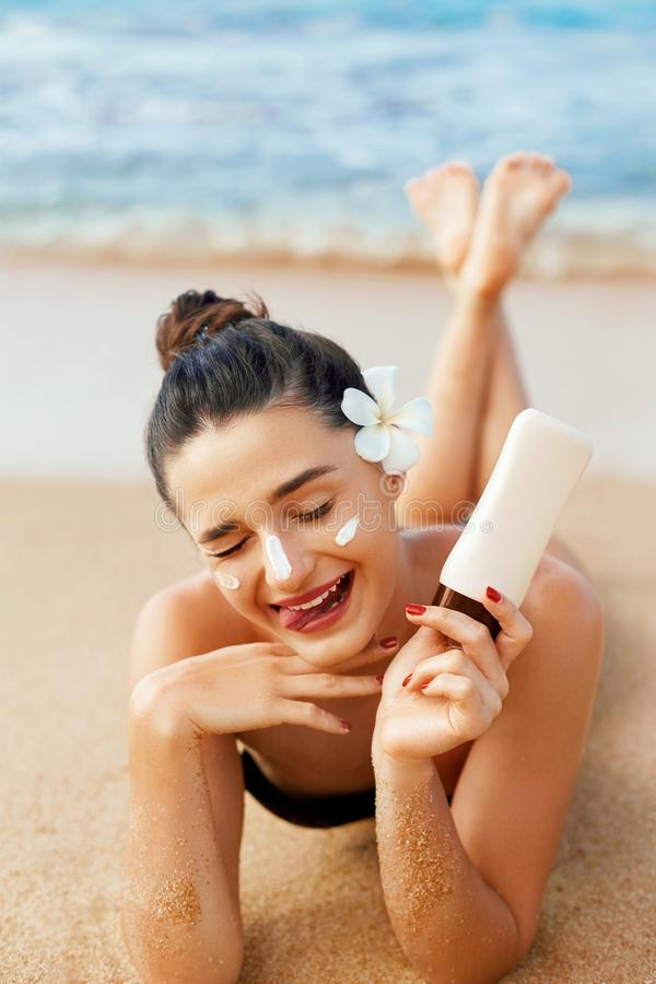 Beauty Woman Skin care sunscreen  holding bottles in her hands. Suntan Girl applying sun cream on face. royalty free stock photos