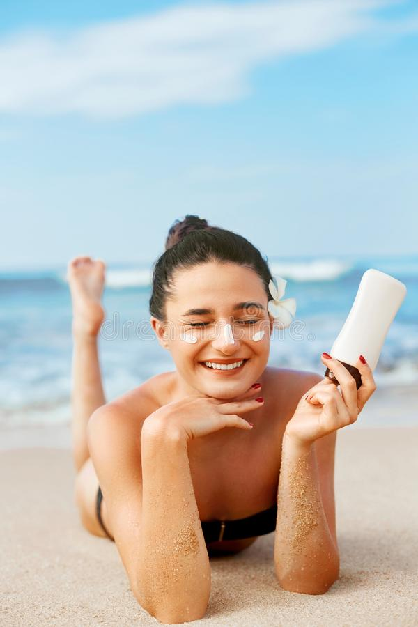 Beauty Woman Skin care sunscreen  holding bottles in her hands. Suntan Girl applying sun cream on face. royalty free stock image