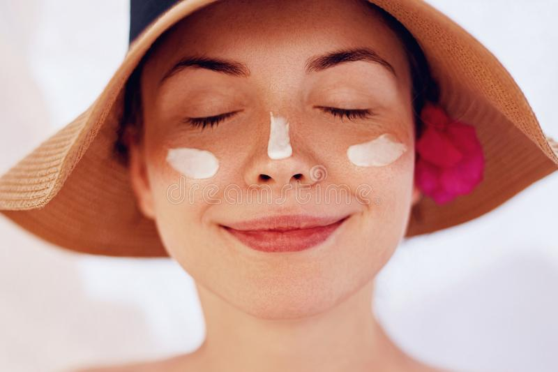 Beauty Woman smile applying sun cream  on face. Skin care. Body Sun protection. royalty free stock image