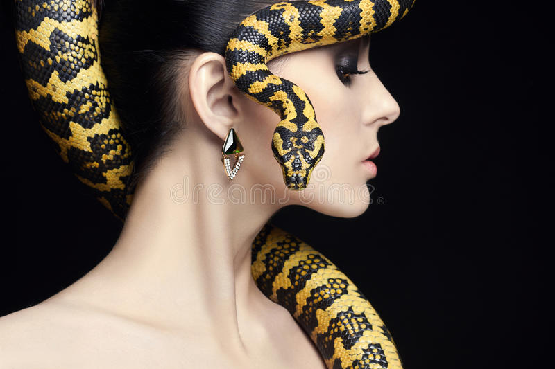 Beauty woman, snake, jewelry and make-up royalty free stock photo