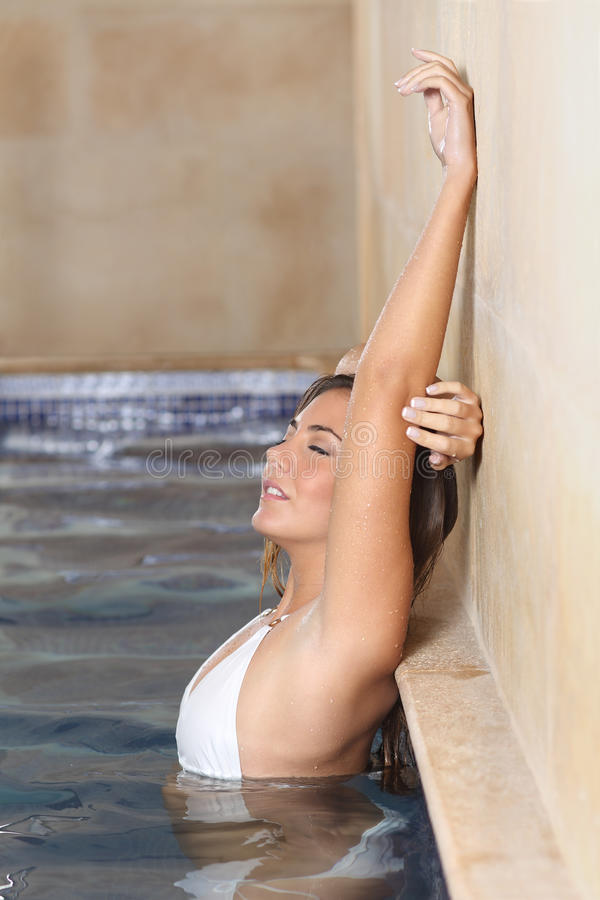 Beauty woman in a spa showing her laser hair removal armpit. Beauty woman bathing in a spa posing showing her laser hair removal armpit royalty free stock photos