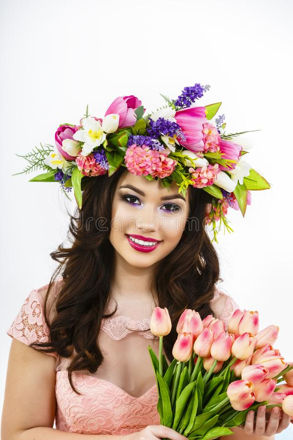 Beauty Woman with Spring Flower bouquet. Beautiful girl with a B. Unch of colorful Tulip flowers. easter makeup and celebration hairstyle stock photo