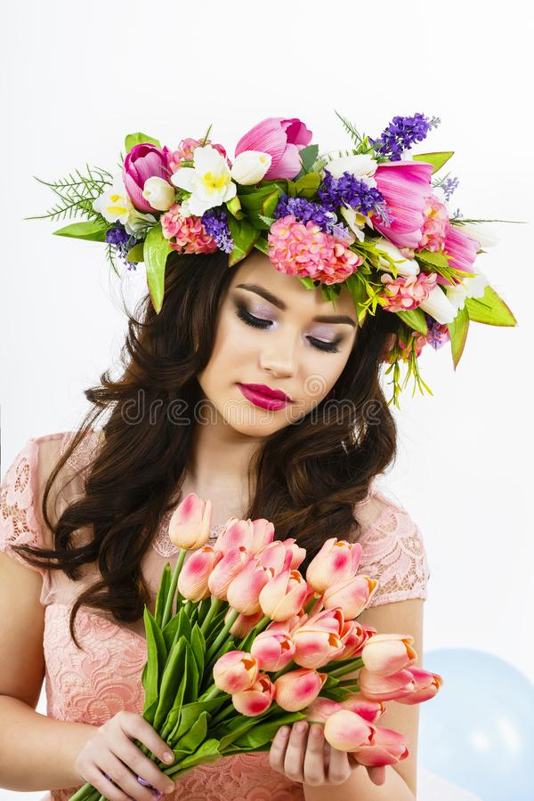 Beauty Woman with Spring Flower bouquet. Beautiful girl with a B. Unch of colorful Tulip flowers. easter makeup and celebration hairstyle royalty free stock images