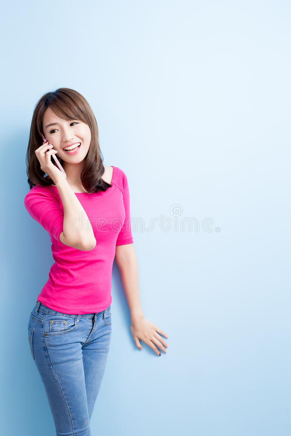 Beauty woman talk on phone. On blue background stock photography