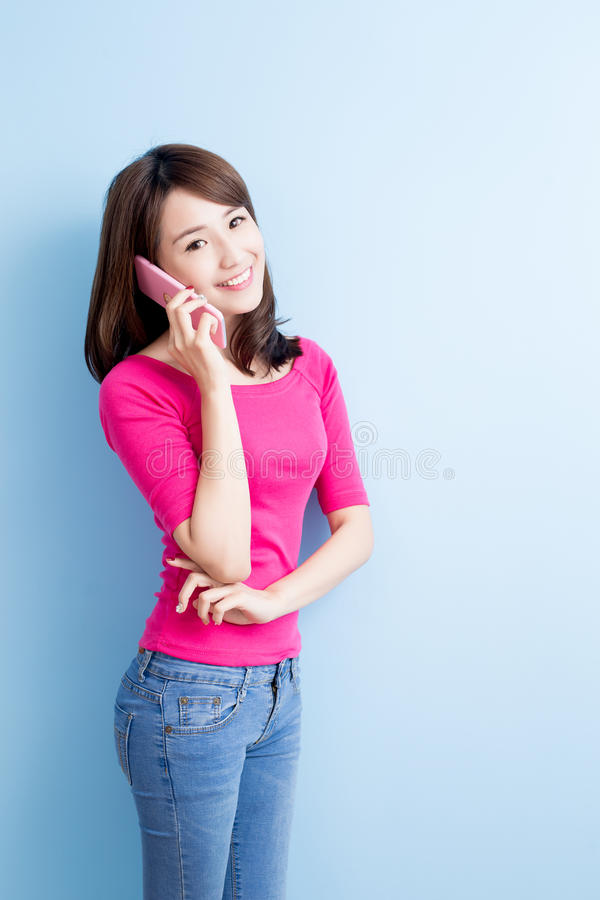 Beauty woman talk on phone. Isolated on blue background stock photo