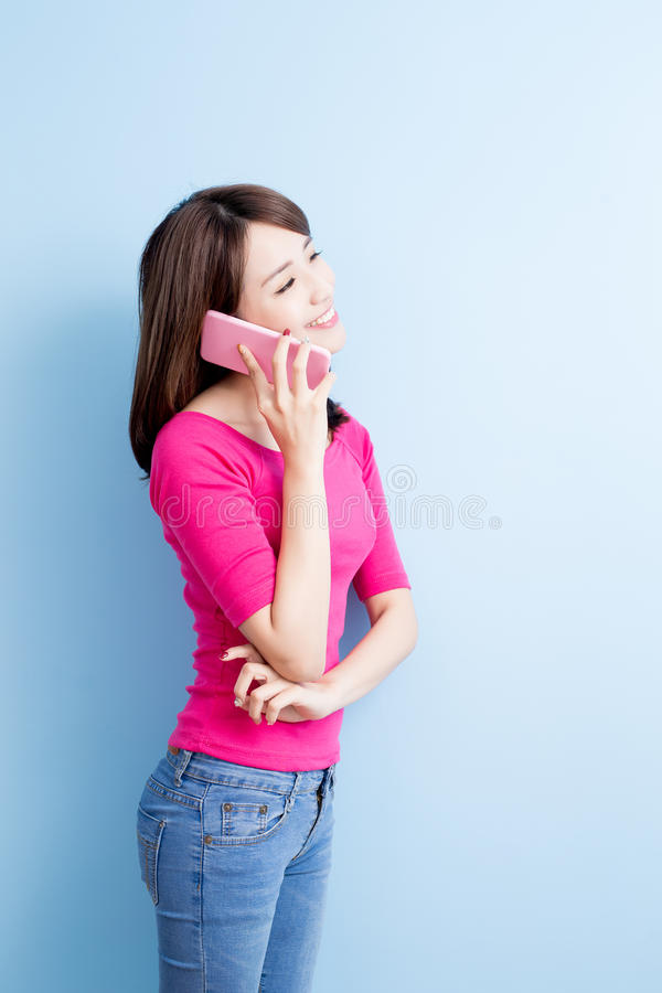 Beauty woman talk on phone. Isolated on blue background royalty free stock photo