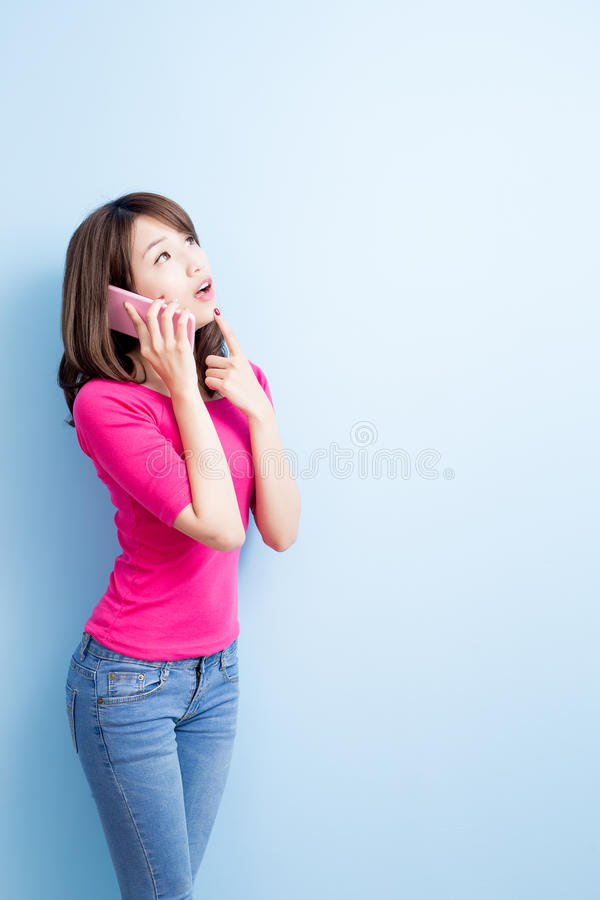 Beauty woman talk on phone. Isolated on blue background royalty free stock photography