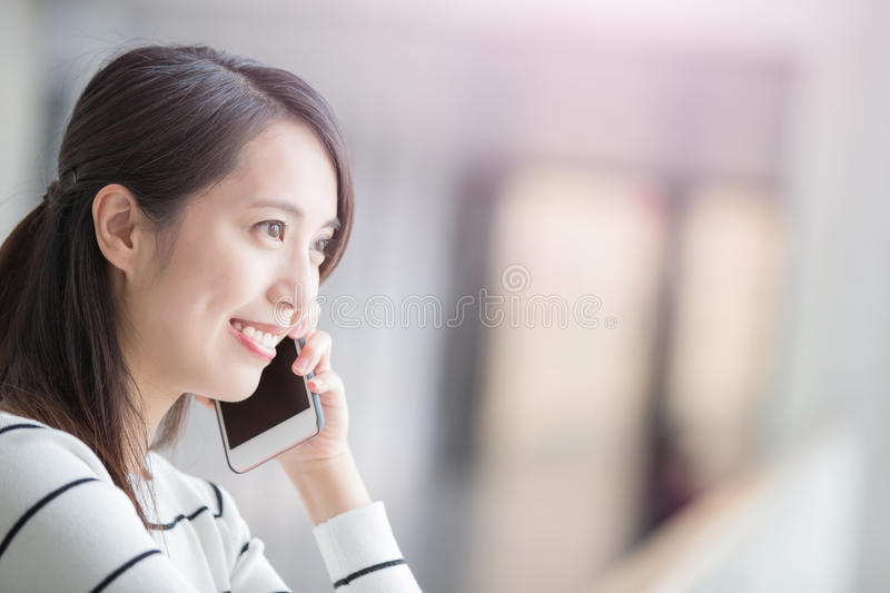Beauty woman talk on phone. And look somewhere in hongkong stock image