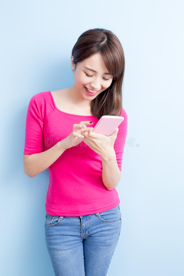 Beauty woman use cellphone. On blue background royalty free stock images