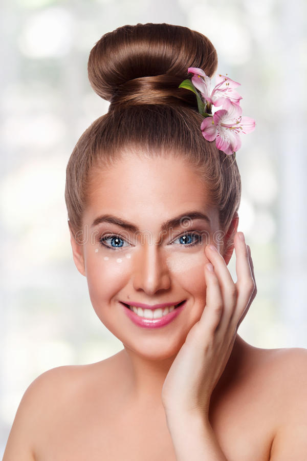 Beauty woman using concealer. Beautiful young woman putting on concealer under eyes royalty free stock photo