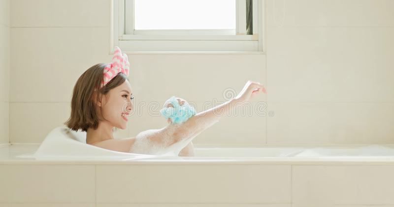 Woman wash body in bathtub. Beauty woman wash body and feel relax in bathtub royalty free stock images