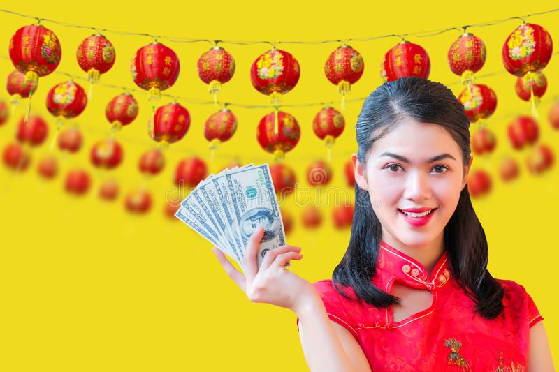 Beauty woman wear cheongsam and Hold a dollar chinese new year on yellow background. Beauty woman wear cheongsam and Hold a dollar chinese new year on a yellow stock photo