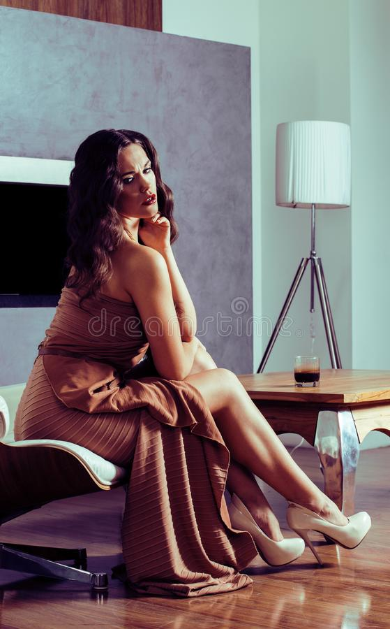 Beauty yong brunette woman sitting near fireplace at home, winte. R warm evening in interior, waiting to celebrate stock images