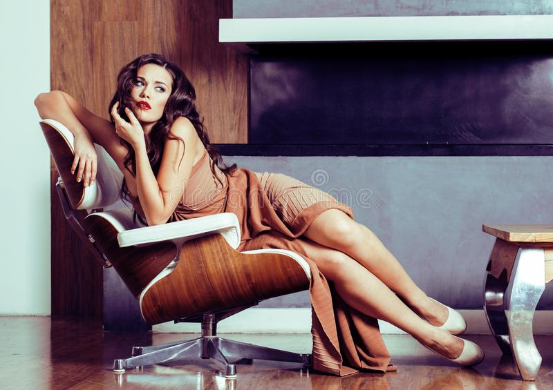Beauty yong brunette woman sitting near fireplace at home, winte. R warm evening in interior, waiting to celebrate stock image