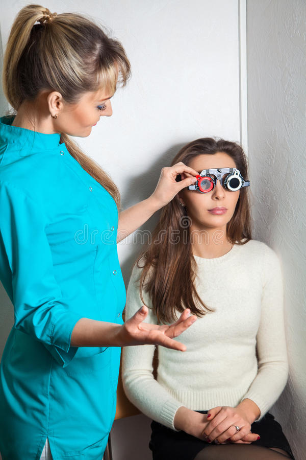 Beauty young adult woman checks vision in an ophthalmologist wit. Beauty young adult women checks vision in an ophthalmologist with corrective lenses stock photo