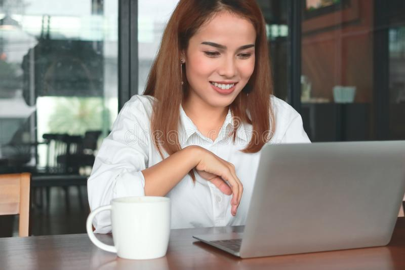 Beauty young Asian business woman with laptop working in modern office. royalty free stock image