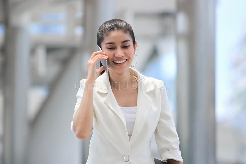 Beauty young Asian business woman talk on phone during walking to office.  royalty free stock images