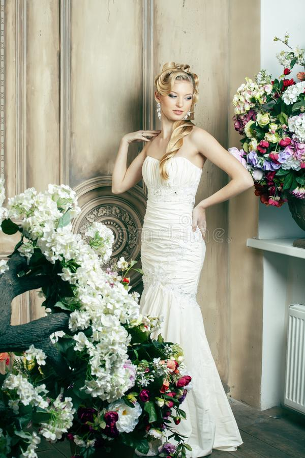 Beauty young bride alone in luxury vintage interior with a lot of flowers, makeup and creative hairstyle stock photos
