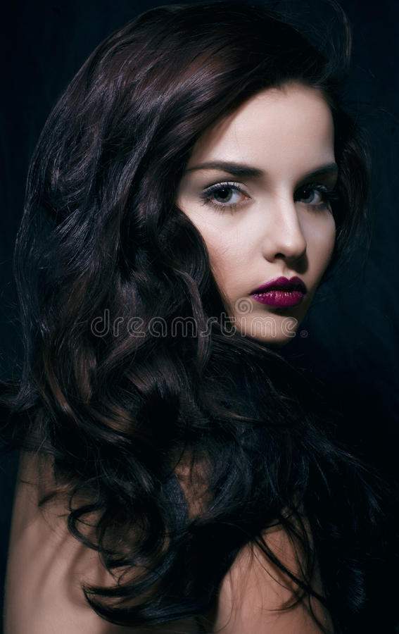 Beauty young brunette woman with curly flying hair, femme fatal on black background, low key royalty free stock photos