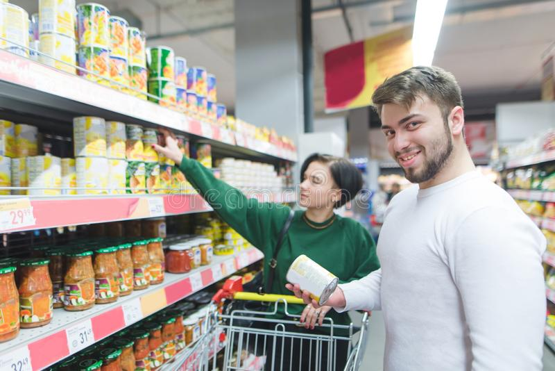 The beauty of a young couple buys canned vegetables in a supermarket. Portrait of a smiling man in a supermarket stock photos