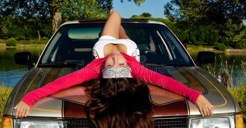 Beauty young girl lay on car at summer sunset royalty free stock photo