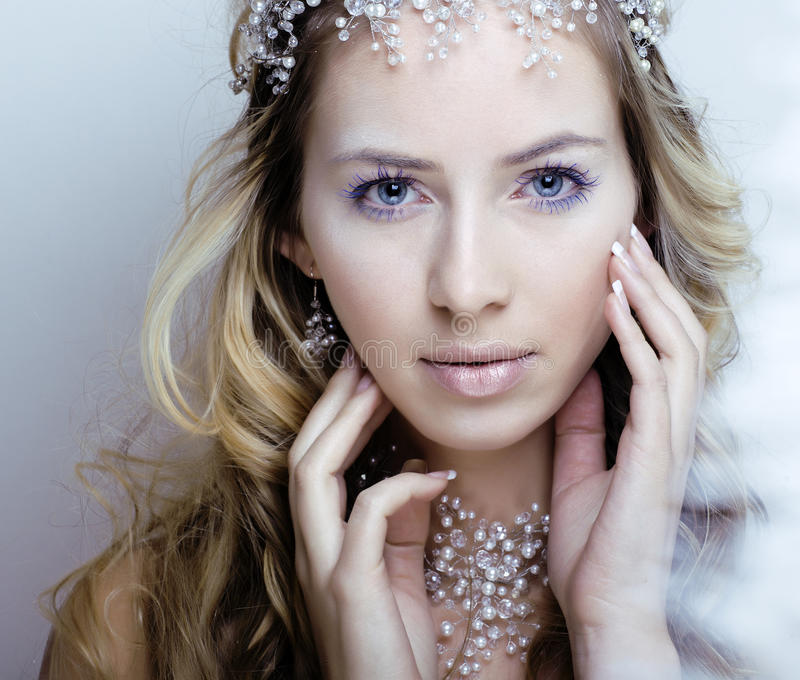 Beauty young snow queen in fairy flashes with hair. Crown on her head close up royalty free stock images
