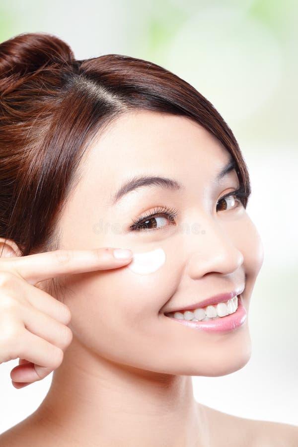 Beauty young woman applying cosmetic cream stock photo