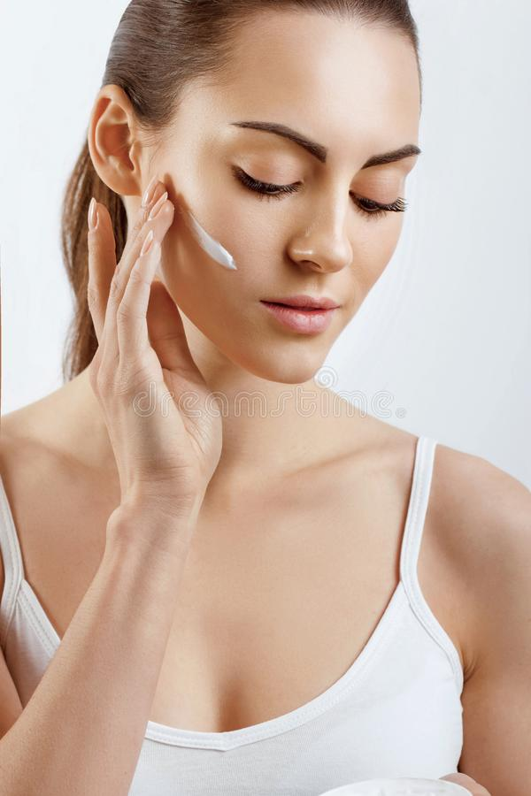 Beauty Young woman applying cream to her face. Skincare and cosmetics concept.Cosmetics. Woman face skin care. Beauty Young woman applying cream to her face stock image
