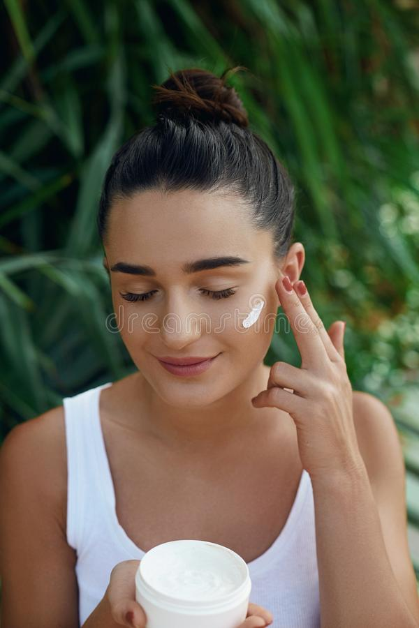 Beauty young woman applying cream to her face. Skin care and cosmetics concept. Cosmetics. Woman face skin care.Natural makeup, touching face stock image
