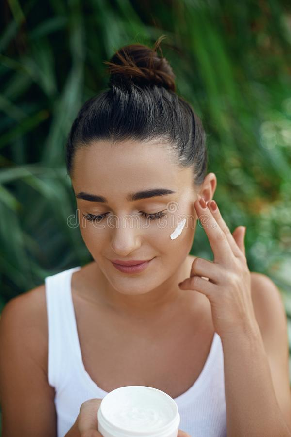 Beauty young woman applying cream to her face. Skin care and cosmetics concept. Cosmetics. Woman face skin care.Natural makeup, to. Uching face royalty free stock image