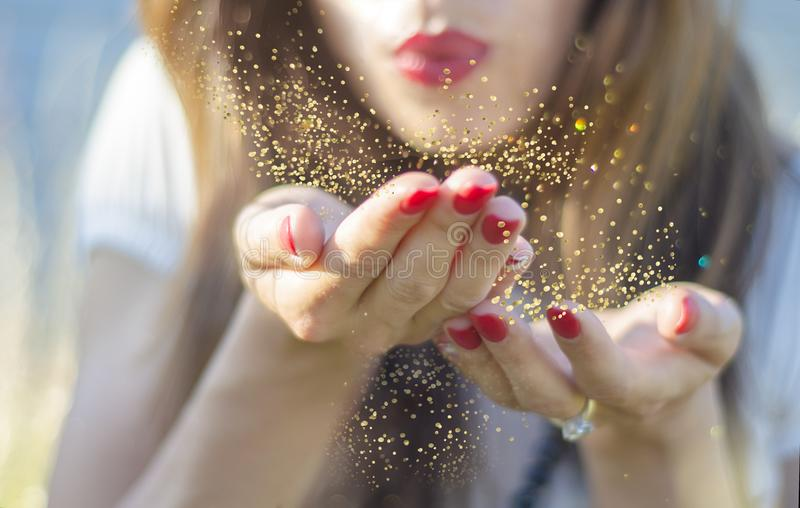 Young woman blowing magic gold dust from her hand stock photos