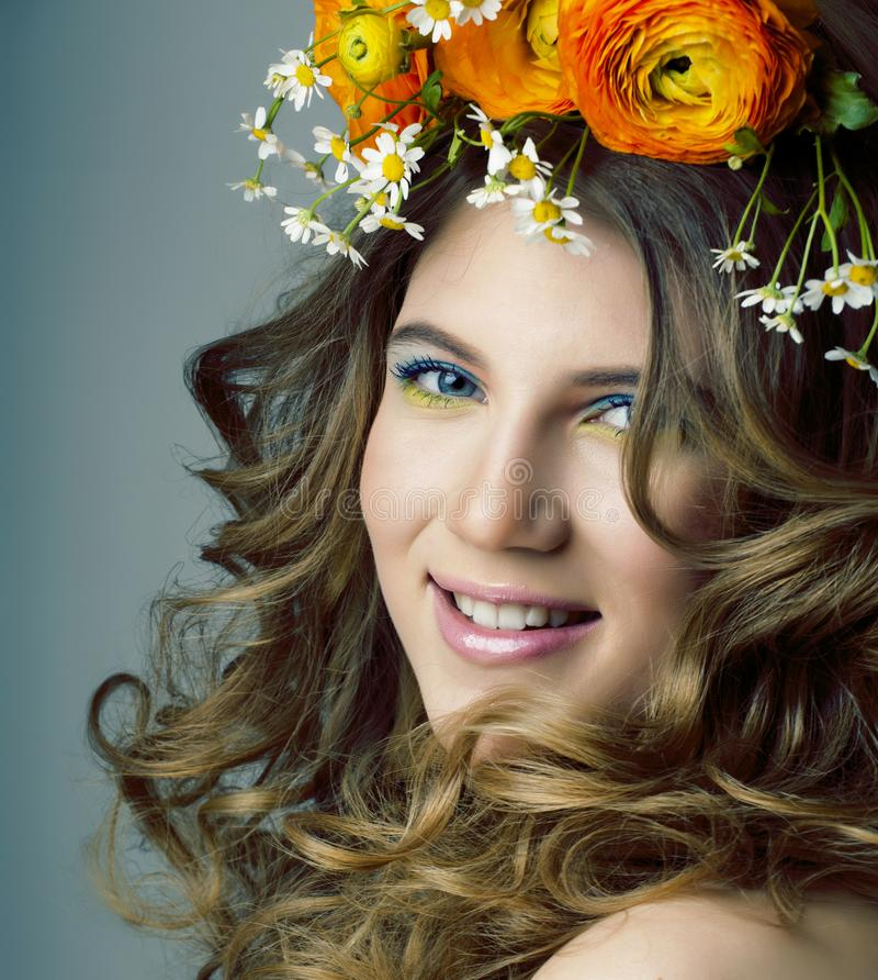 Beauty young woman with flowers and make up close up, real spring curly blond girl royalty free stock images