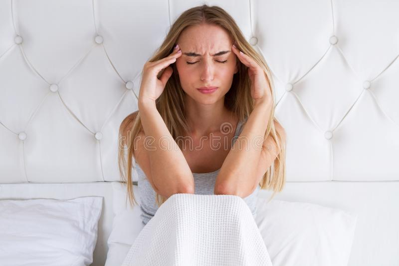 Beauty, young woman with headache. Upset woman having a migraine lying on a bed at home stock photo