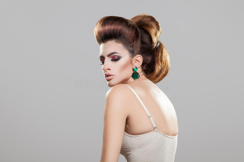 Beauty young woman with healthy skin creative hairstyle and nice. Makeup in studio on gray background royalty free stock image