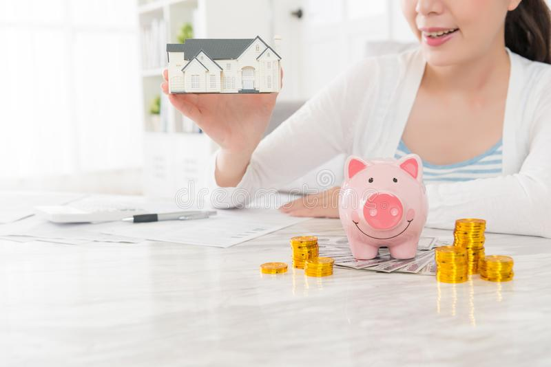 Beauty young woman holding little house model. Closeup of beauty young woman holding little house model and counting account coin cash piggy bank planning buying royalty free stock image