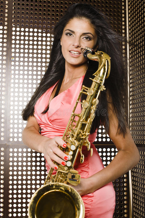 Beauty young woman playing on saxophone royalty free stock photography