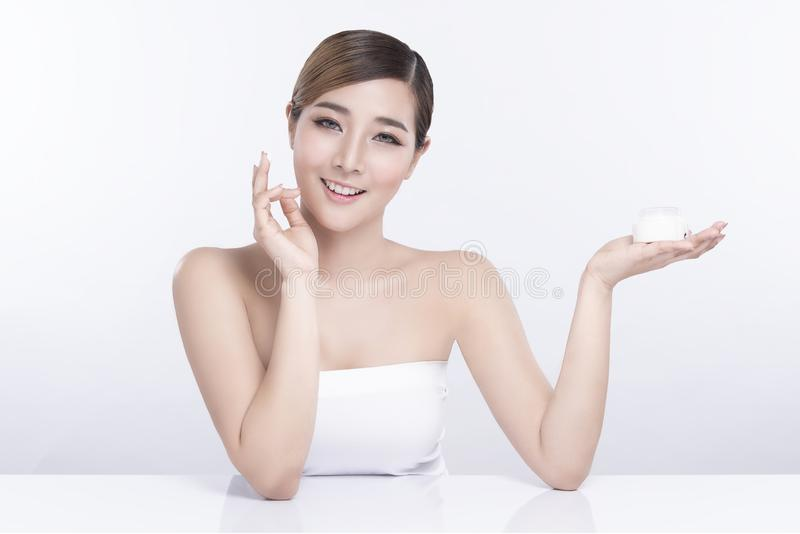 Beauty young woman showing moisturizing cream product on white background. treatment & Skin care concept royalty free stock images