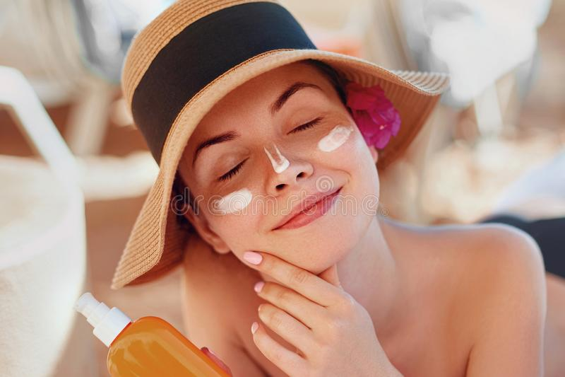 Beauty Young woman with sun cream on face holding sunscreen bottle on the beach royalty free stock photography