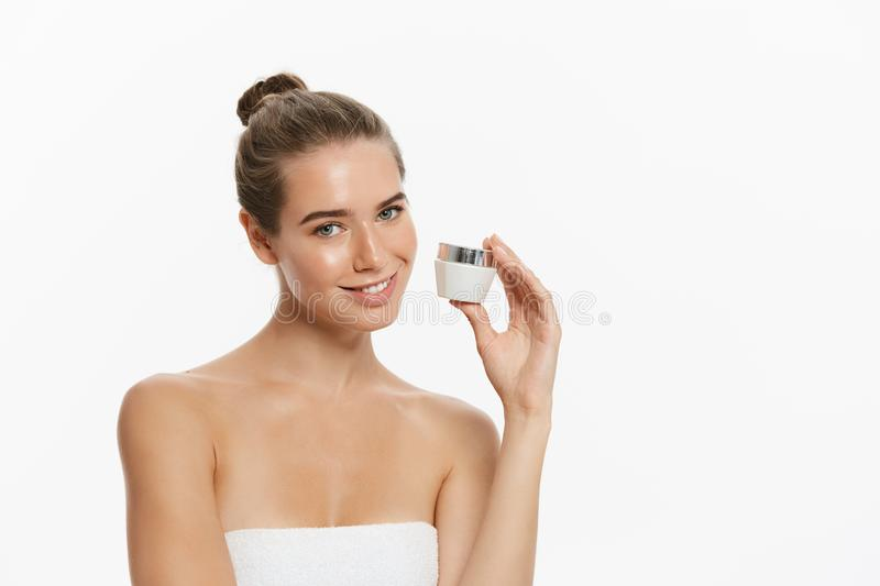Beauty Youth Skin Care Concept - Beautiful Caucasian Woman Face Portrait holding and presenting cream tube product. Beautiful Spa model Girl with Perfect Fresh royalty free stock photo