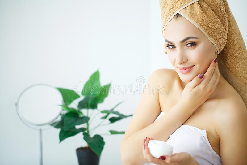 Beauty Youth Skin Care Concept - Close up Beautiful Caucasian Woman Face Portrait applying some cream to her face for skin care. royalty free stock photo