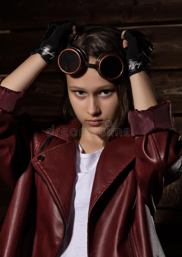 Beautyful Girl in leather jacket in a dark. Mysterious disobedient child, problems with early growing girls royalty free stock photo