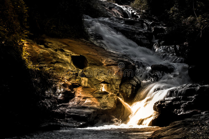 Beautyful Mystery night yellow light at deep tropical rain forest with flowing cascade waterfall stock photography