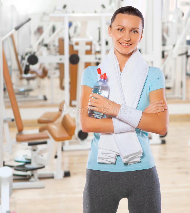 Beautyful smiling standing sportswoman with bottle of water in g royalty free stock image