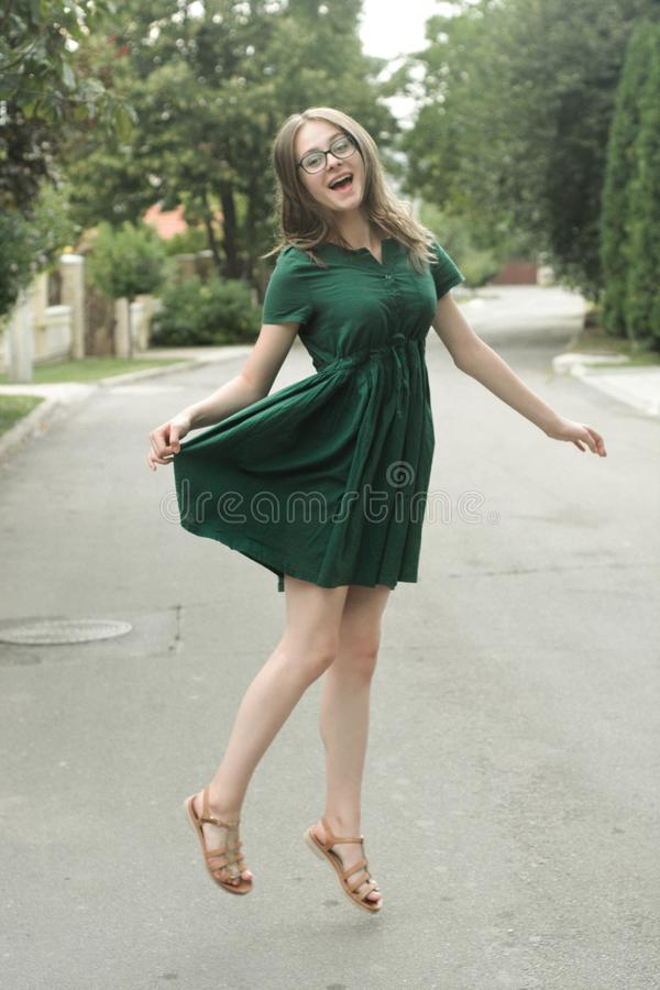Beautyful teen age girl in green dress, jumping. Summer day. Free happy woman stock photo