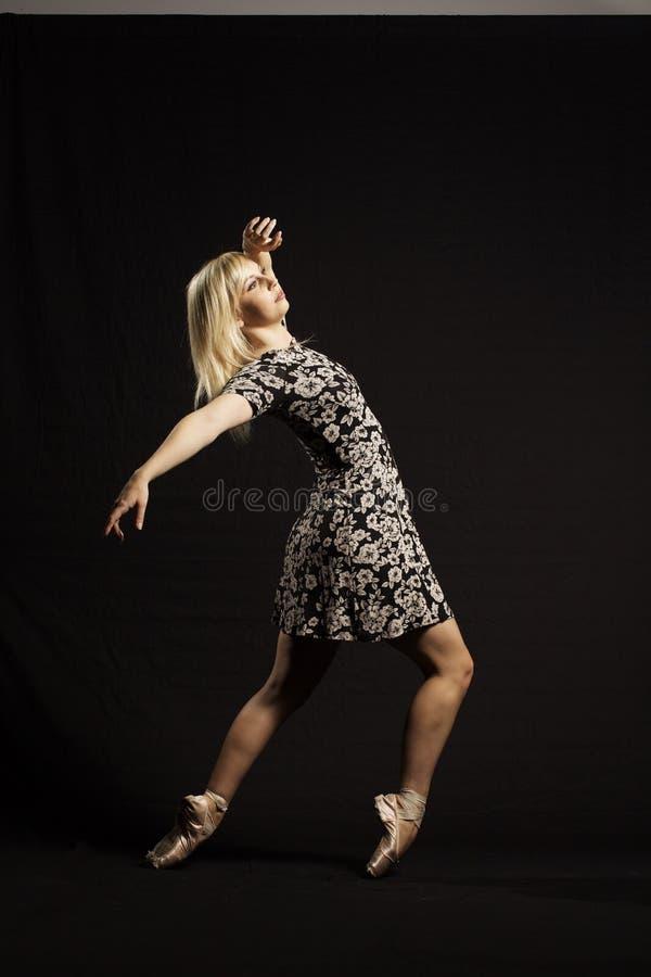 Beauutyvrouw met lang blondehaar die op zwarte achtergrond dansen royalty-vrije stock foto's