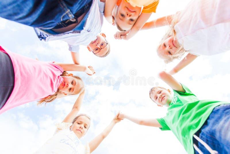 Beaux écoliers se tenant en cercle tenant des mains  photographie stock