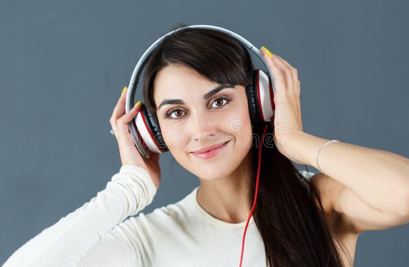 Beaux écouteurs de port de sourire d'une chevelure foncés de femme photos stock