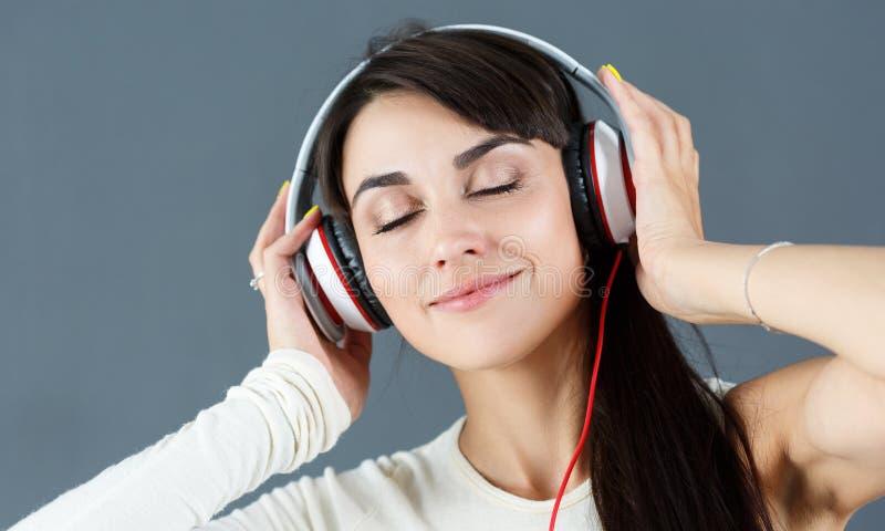 Beaux écouteurs de port de sourire d'une chevelure foncés de femme images libres de droits