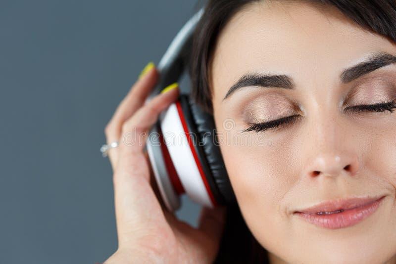 Beaux écouteurs de port de sourire d'une chevelure foncés de femme image stock