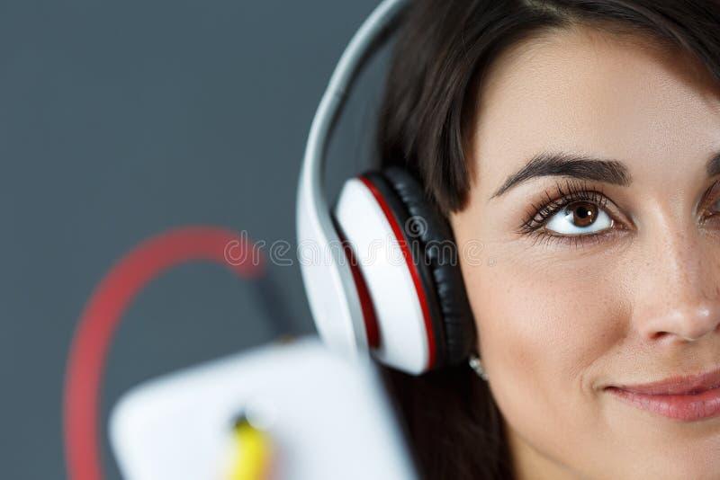 Beaux écouteurs de port de sourire d'une chevelure foncés de femme photographie stock libre de droits